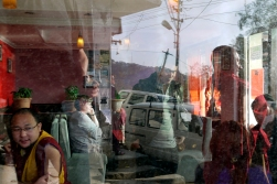 Tibetan monks and Westerners in a cafe near the Dalai Lama's temple