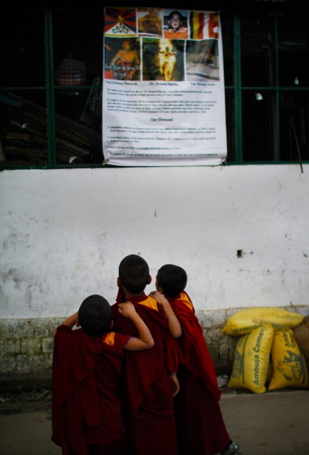 Young Tibetan monks look at a political poster