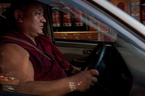 A Tibetan Buddhist monk drives a car through McLeodganj. Photo by Angus McDonald
