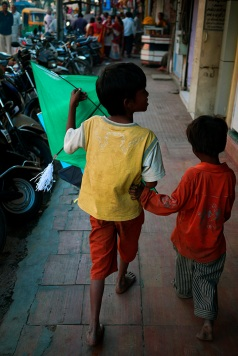 Young boys carry a newly bought kite in Baroda, Gujarat, India ahead of the annual Uttarayan, or Makar Sakranti, kite flying festival. Photo by Angus McDonald