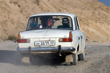 People drive a battered Soviet-era car at Panjikent, Tajikistan. Photo by Angus McDonald
